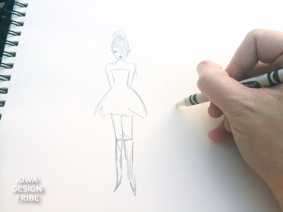 Drawing wings on a fairy figure with a white crayon on white sketch paper